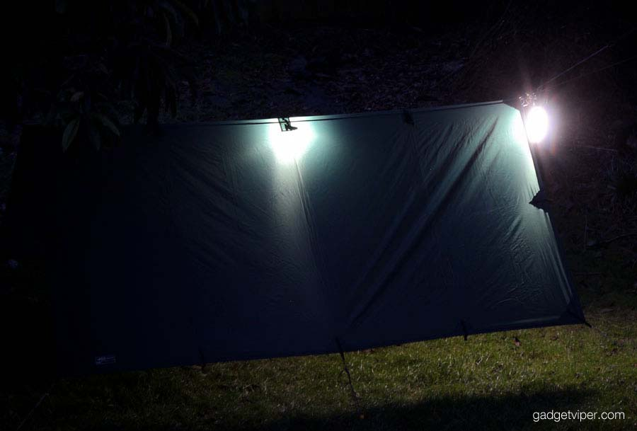 The OxyLED camping lantern lighting up a tarp and hammock set up.