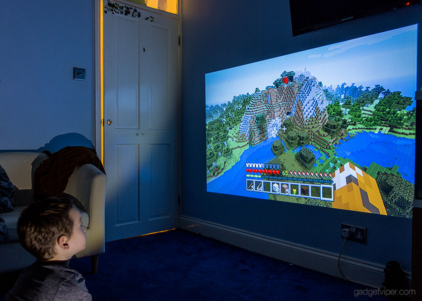 The Mpow mini projector connected to a playstation games console playing minecraft